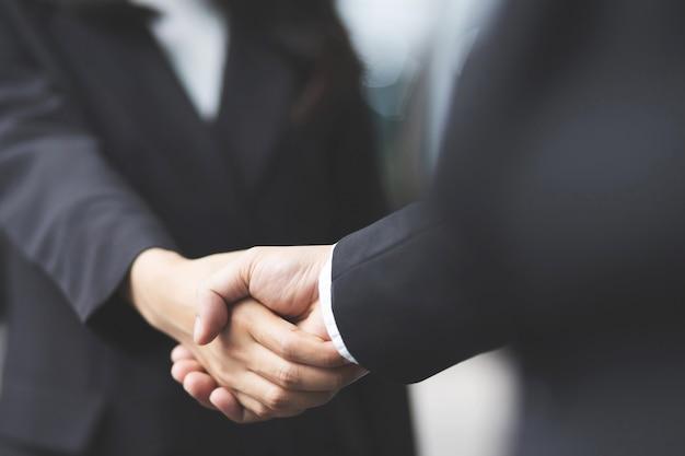 ビジネスマンのクローズアップは、2人の同僚の間で投資家を握手しますok、手をつないでビジネスに成功します。