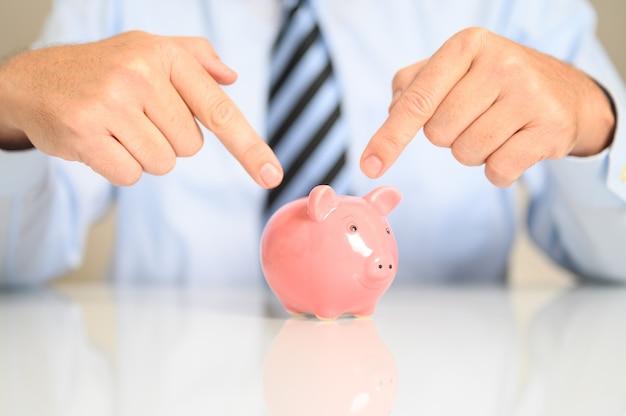 貯金箱を指しているビジネスマンのクローズアップ