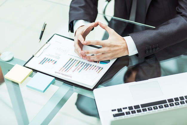 Крупным планом бизнесмен размышляет о финансовой политике компании, сидя за столом в офисе