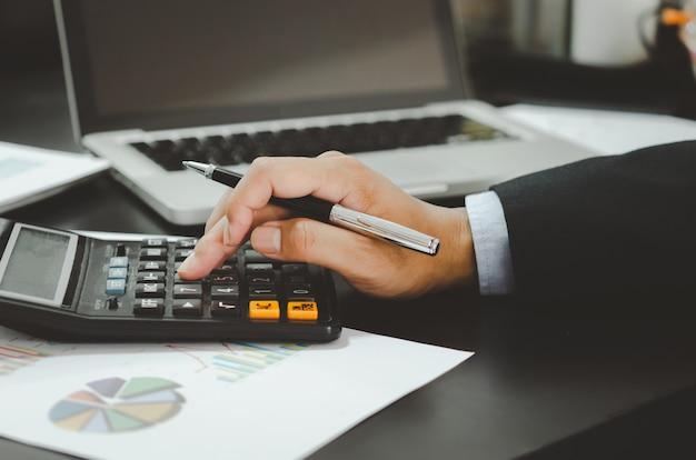 Крупный план руки бизнесмена и калькулятора. бизнес, финансы, инвестиции, налоги и концептуальная экономика