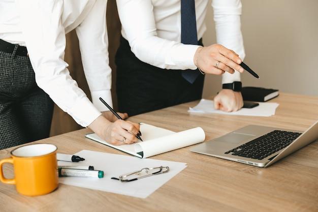 ラップトップを使用し、オフィスのデスクでノートにメモを書く実業家と秘書のクローズアップオフィスチームワークビジネスプランの議論
