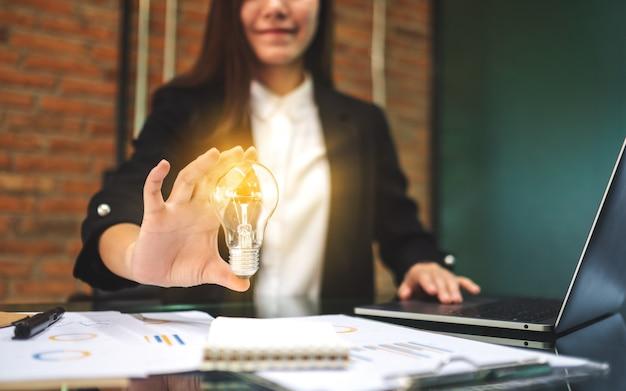 사무실에서 노트북 컴퓨터와 서류 작업을하는 동안 빛나는 전구를 들고 사업가의 근접 촬영