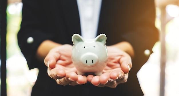 お金と金融の概念を節約するための貯金箱を保持している実業家のクローズアップ