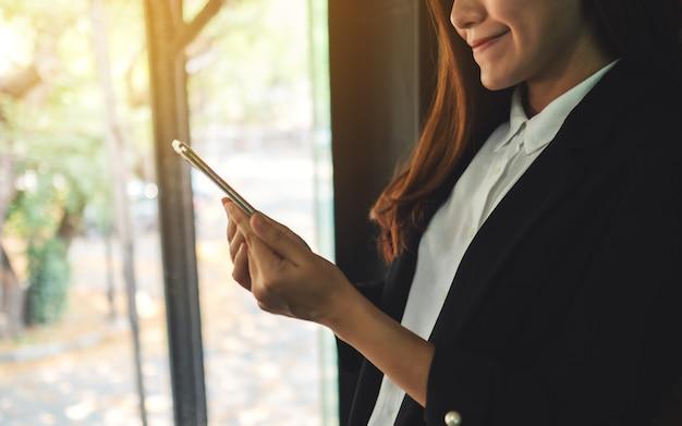 Крупным планом бизнесвумен, проведение и использование мобильного телефона в помещении