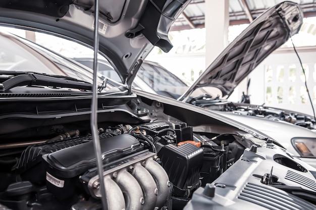 固定のための自動車のガレージに駐車された車のエンジンのクローズアップ
