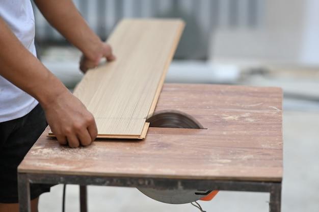 木製の作業台の機器で作業している大工の手のクローズアップ。