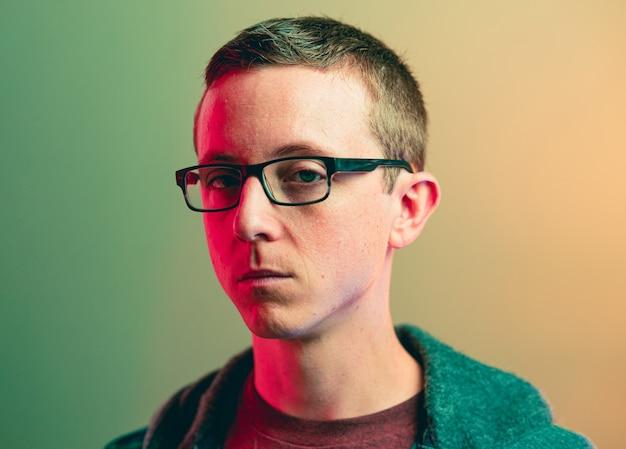 붉은 빛 효과와 안경을 쓰고 포커 얼굴을 가진 백인 남자의 근접 촬영