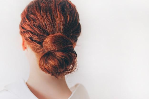 白人の赤髪の若い女性のクローズアップ。女性モデルは、カールしたカールを束ねています。