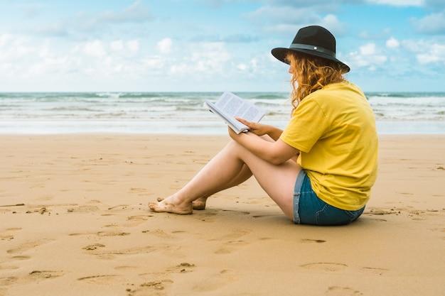 Крупный план кавказской женщины в шляпе и желтой футболке, читающей книгу на пляже