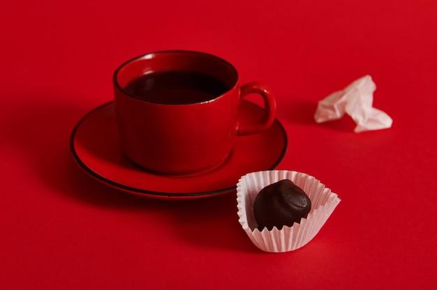 チョコレートトリュフとチョコレートプラリネからのしわくちゃの紙のラッパーの隣に、赤い受け皿のコーヒーとセラミックコーヒーカップのクローズアップ。コーヒーとチョコレートの日のコンセプト
