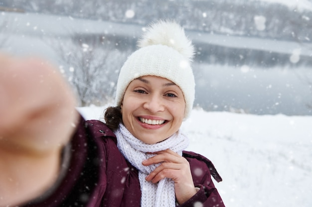 雪が降るのを楽しんでいる自分撮りをしながらカメラに微笑んで陽気なブルネットの女性のクローズアップ