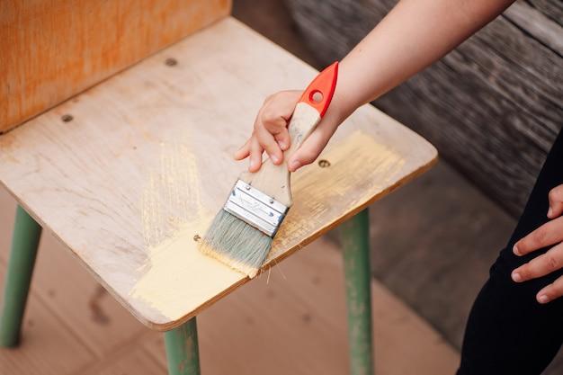 Крупным планом рука ребенка держит кисть и рисует деревянный стул для повторного использования