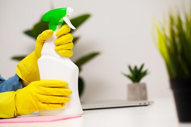 Крупным планом работника клининговой компании очищает офис