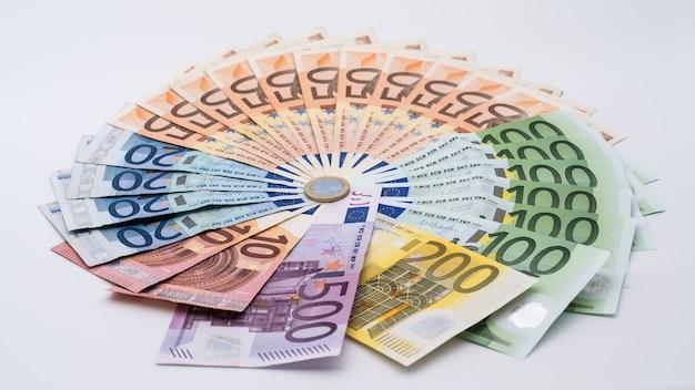 さまざまな価値の紙幣を使用した1ユーロの硬貨のクローズアップ。現金の背景。本当の百ユーロ。良い収益。給与の発行。クレジットパーセント。成功したビジネス