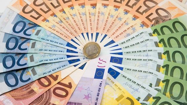 Крупным планом монета один евро с банкнотами разного достоинства. наличные деньги фон. настоящие сто евро. хороший заработок. выдача зарплаты. кредитный процент. успешный бизнес