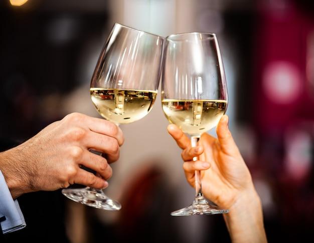 白ワイングラスを乾杯するカップルのクローズアップ