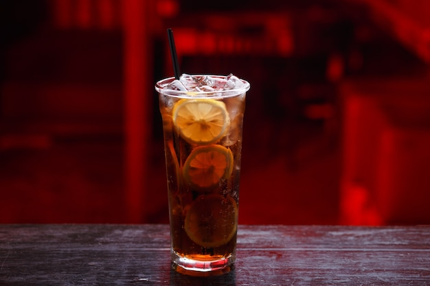 Крупный план коктейля cuba libre в длинном стакане, джин, стоя на барной стойке, изолированном на пространстве красного света.