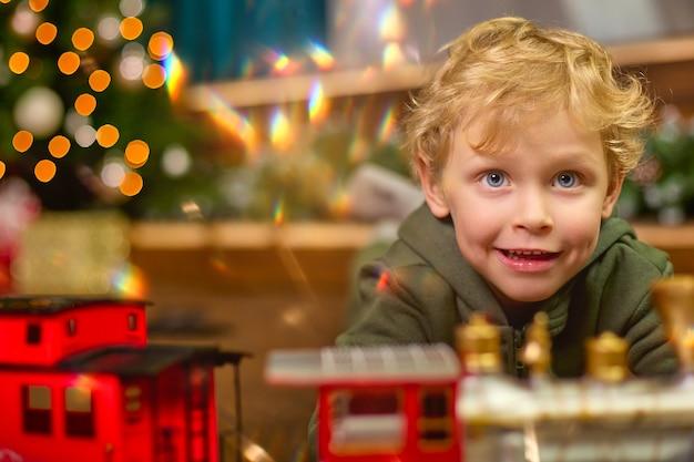 クリスマスツリーで魔法のおもちゃの列車で遊ぶ縮れ毛の少年のクローズアップ