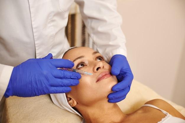Крупным планом лицо милой женщины и руки косметологов в синих медицинских защитных перчатках, держа шприц с косметическим продуктом возле ее лица