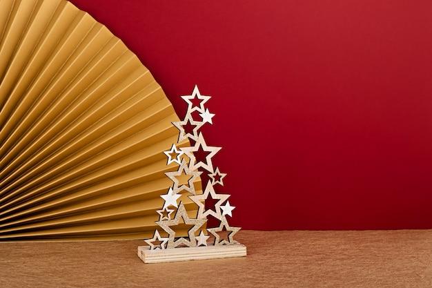 종이 팬을 가진 황금 별 만든 장식 크리스마스 트리의 근접 촬영. 진홍색 벽에 세련된 현대 크리스마스 장식