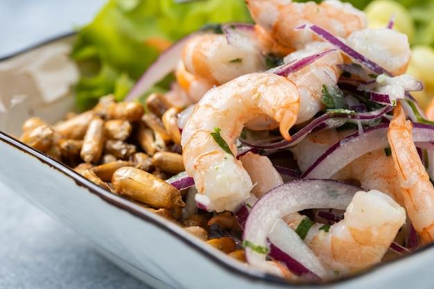 Крупным планом вкусный салат с морепродуктами и овощами в миске на столе