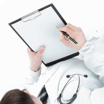 彼の手で患者の地図を保持している医師のクローズアップ。白で隔離