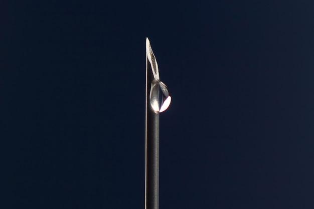 医療注射針の先端に一滴の薬のクローズアップ