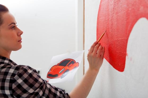 Художница в черно-белой рубашке крупным планом рисует карандашом красную машину на стене