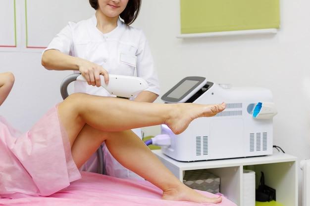 Крупным планом женщина-косметолог делает молодой женщине процедуру лазерной эпиляции на ноге