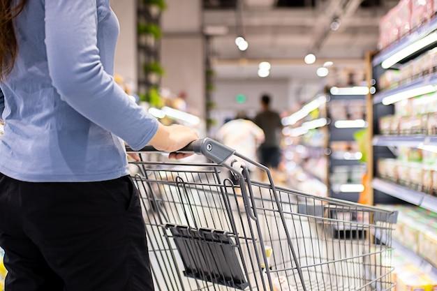 スーパーマーケットで買い物をするトロリーカートと女性の手のクローズアップ
