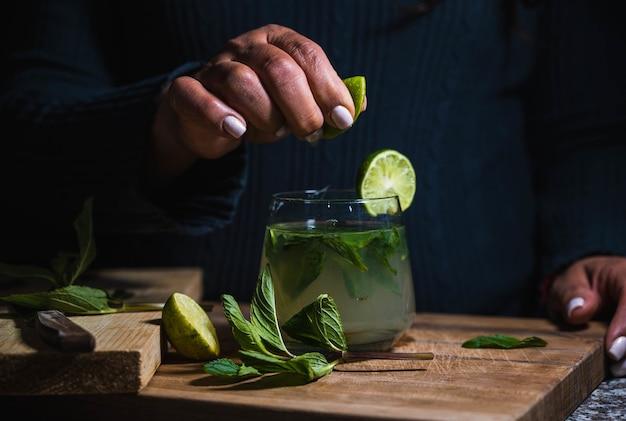 민트 음료와 함께 레모네이드 한 잔에 레몬을 짜내는 여성의 근접 촬영