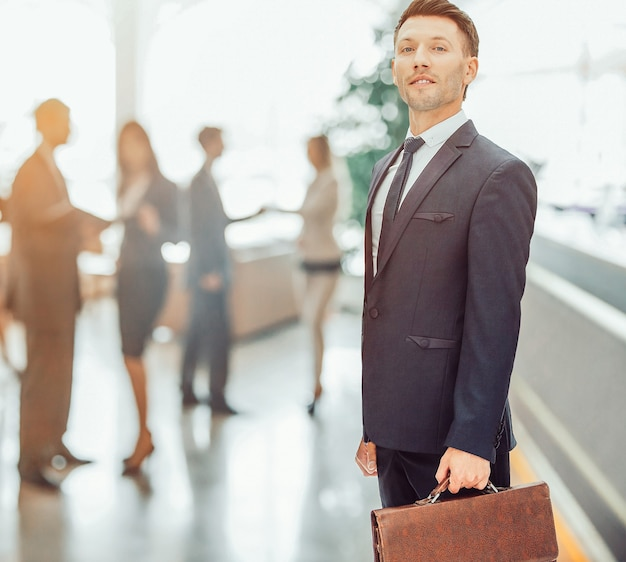 Крупным планом финансового менеджера в черном деловом костюме с портфелем на фоне сотрудников офиса. на фото есть пустое место для вашего текста