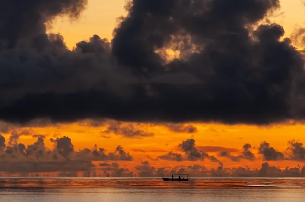 その上に大きな暗い雲とオレンジ色の地平線上の漁船のクローズアップ