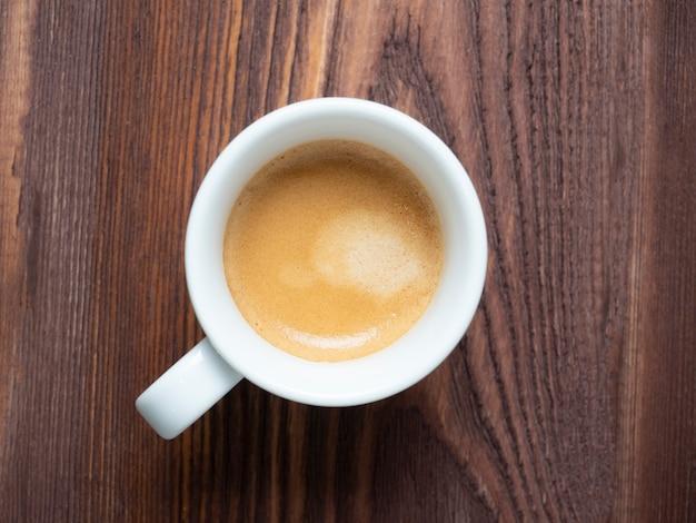 テクスチャード加工の木製の背景に白いカップの香りのコーヒーのクローズアップ