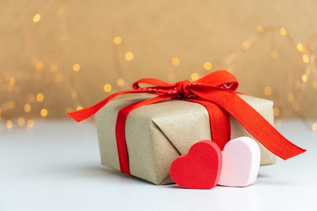 Крупным планом подарочная коробка с красной лентой и двумя сердечками на размытом фоне