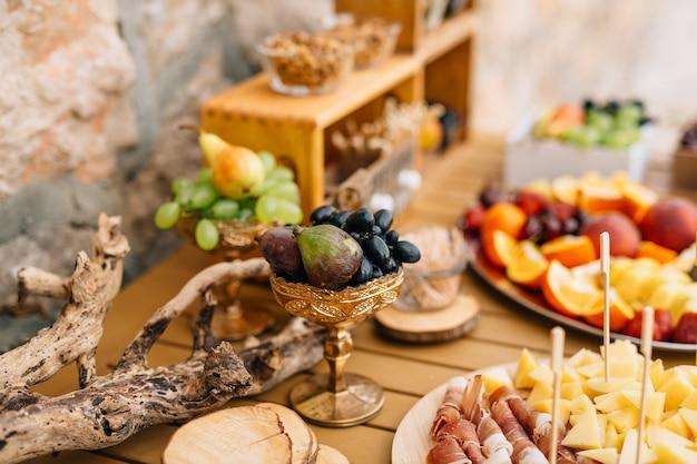 접시에 슬라이스 햄 치즈와 과일 테이블에 포도와 무화과의 도금 한 그릇의 근접 촬영