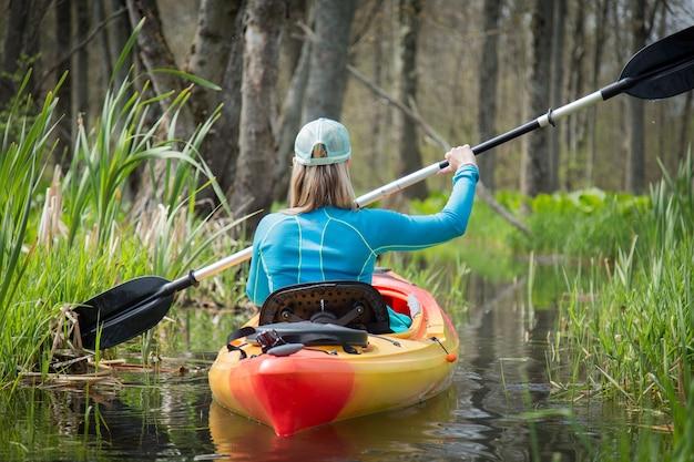 낮에는 햇빛 아래 녹지로 둘러싸인 작은 강에서 카약을 타는 소녀의 근접 촬영