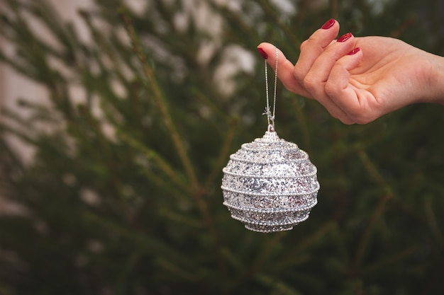 Крупным планом руки девушки с серебряным шаром, усыпанным конфетти, украшают елку