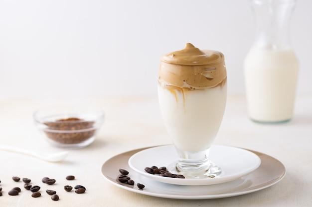 コーヒー豆が置かれたテーブルの上のダルゴナ コーヒーのグラスのクローズ アップ