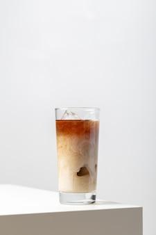 白のテーブルの上のミルクとアイスティーのガラスのクローズアップ