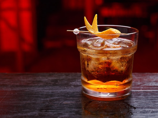 Крупный план коктейля отца бога в коротком стакане, джине, стоящем на барной стойке, изолированном на пространстве красного света. горизонтальный вид.