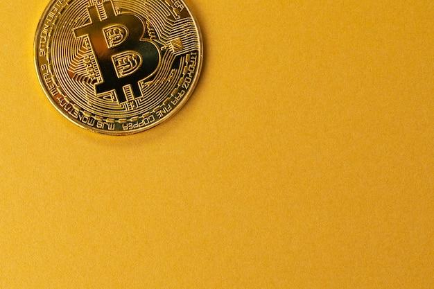 ゴールドビットコインコインのクローズアップ仮想通貨またはブロックチェーン暗号通貨大きなコピースペースゴールドイエローの背景