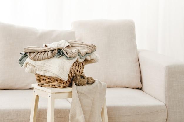近くの小さなテーブルに折りたたまれた服のバスケットが置かれた灰色のソファのクローズ アップ