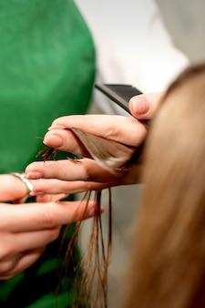 Крупным планом парикмахер стрижет кончики волос клиентки в салоне красоты