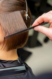 Крупным планом парикмахер, выпрямляющий короткие каштановые волосы утюгом для волос в парикмахерской