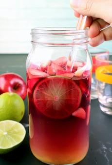 背景のぼやけた成分とグラスボトルの赤ワインサングリアを混合する手のクローズアップ