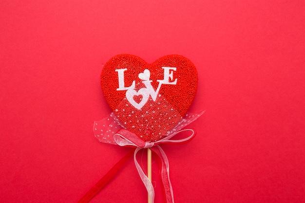 赤い孤立した背景の上の棒の装飾とハートのクローズアップ。白い文字で愛を綴る。