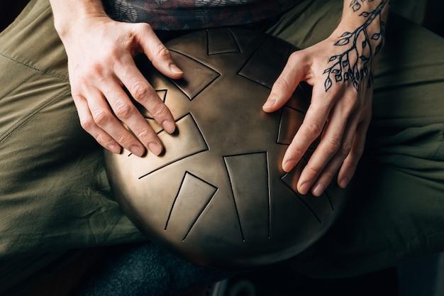 Крупным планом битник, играя танк барабан с руками