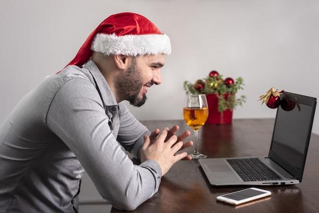 サンタの帽子をかぶって、彼のワインを楽しんで、オンライン会議を持っているヒスパニック系の男性のクローズアップ