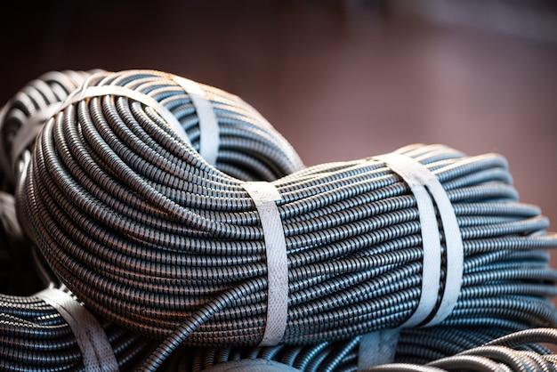 工場または産業プラントで相互接続された金属製の柔軟なチューブの巨大な束のクローズアップ